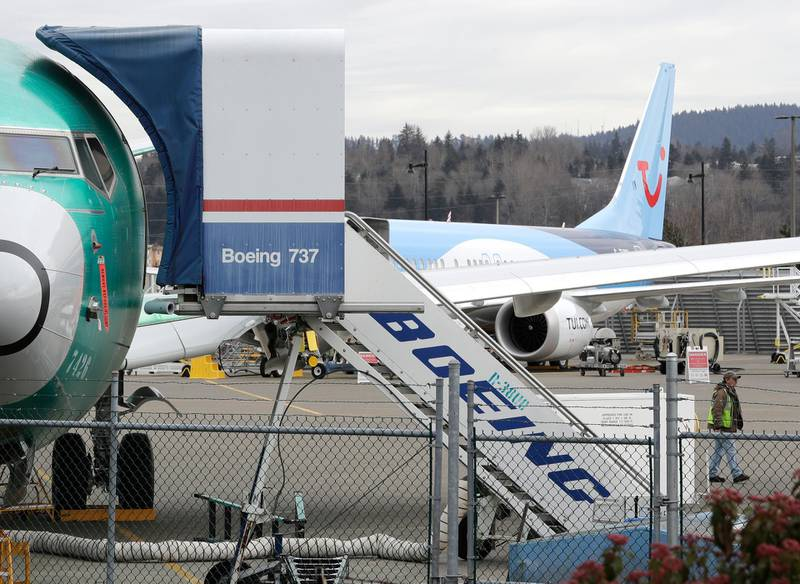 In this Monday, March 11, 2019 file photo, a Boeing 737 MAX 8 airplane being built for TUI Group sits parked in the background at right at Boeing Co.'s Renton Assembly Plant in Renton, Wash. The Transportation Department confirmed that its watchdog agency will examine how the FAA certified the Boeing 737 Max 8 aircraft, the now-grounded plane involved in two fatal accidents within five months. The FAA had stood by the safety of the plane up until last Wednesday, March 13, 2019 despite other countries grounding it.  (AP Photo/Ted S. Warren, File)