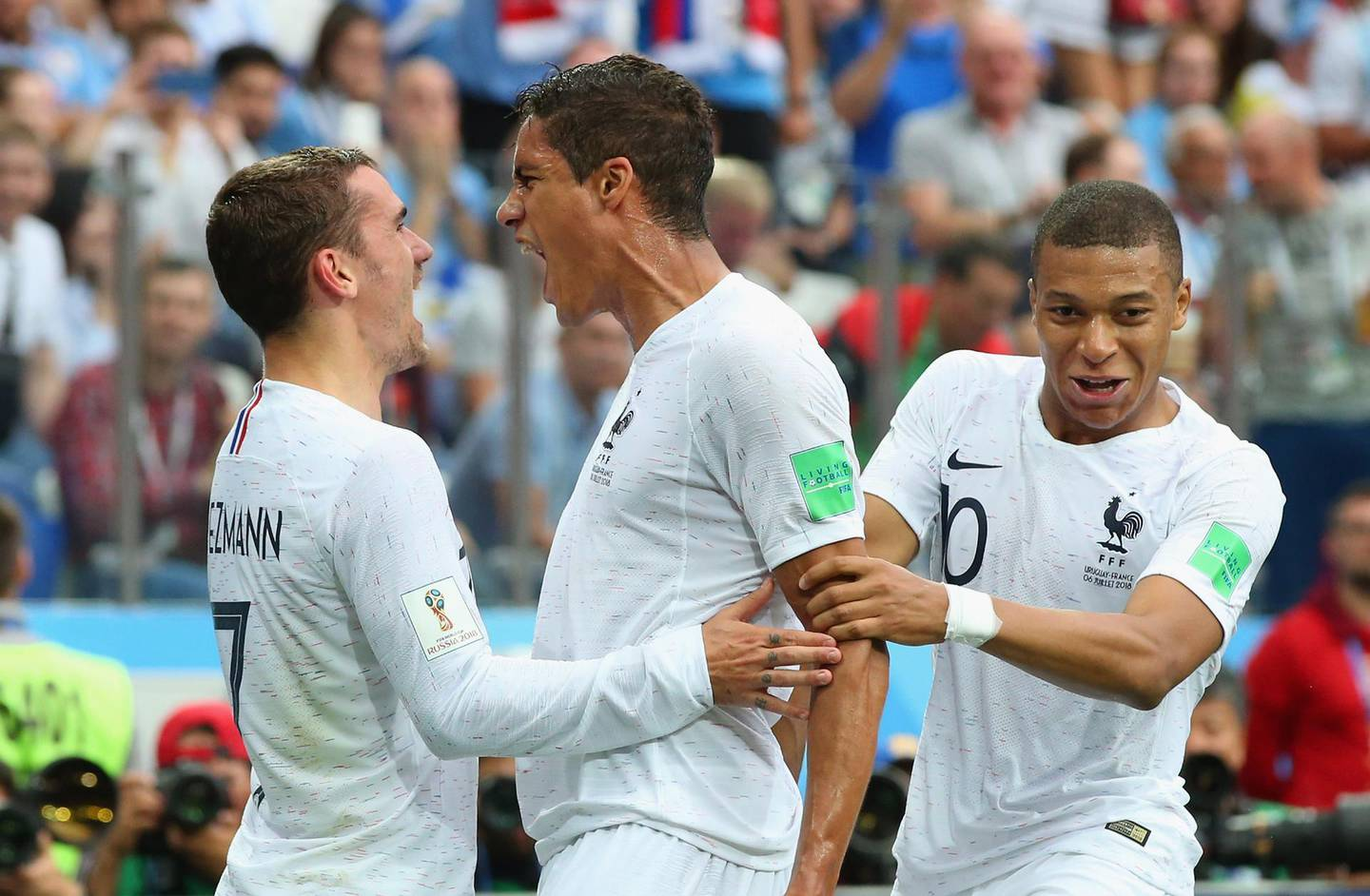 NIZHNY NOVGOROD, RUSSIA - JULY 06:  Raphael Varane of France celebrates with team mates Kylian Mbappe and Antoine Griezmann after scoring his team's first goal during the 2018 FIFA World Cup Russia Quarter Final match between Winner Game 49 and Winner Game 50 at Nizhny Novgorod Stadium on July 6, 2018 in Nizhny Novgorod, Russia.  (Photo by Alex Livesey/Getty Images)