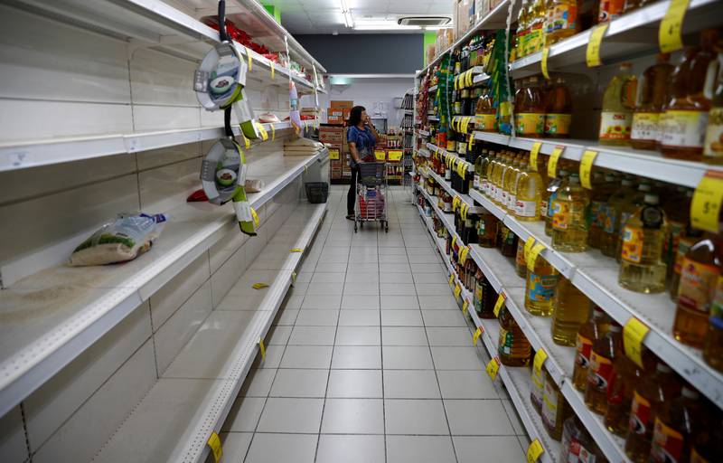 A packet of rice is pictured on an empty shelf as people stock up on food supplies, after Singapore raised coronavirus outbreak alert level to orange, at a supermarket in Singapore February 8, 2020. REUTERS/Edgar Su