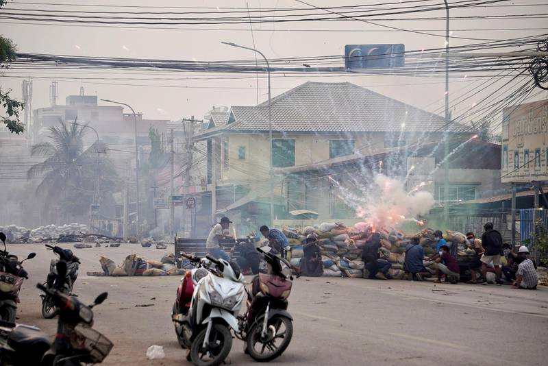 Firecrackers explode as protestors take cover behind a barricade during a demonstration against the military coup in Mandalay, Myanmar March 21, 2021. REUTERS/Stringer