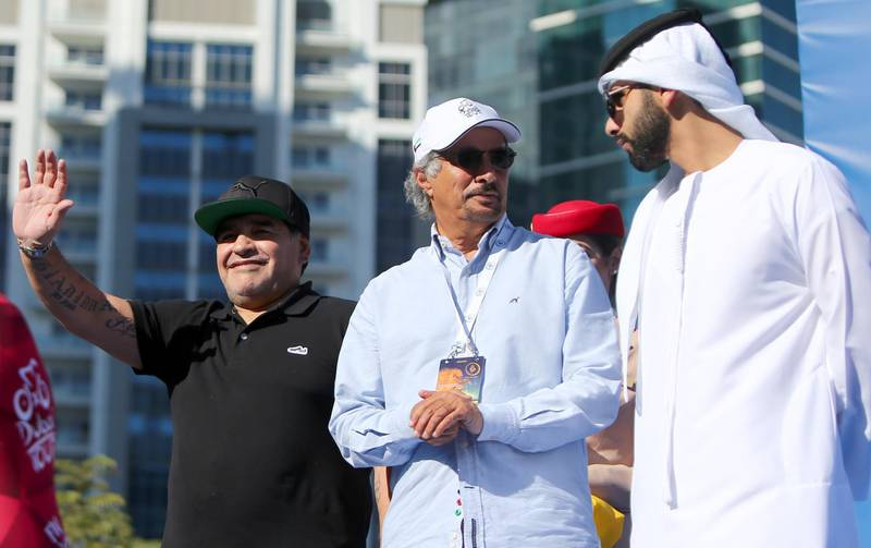 Argentinian legend Diego Maradona (L) waves to crowds as he stands on the podium next to Said Harb (C), Secretary General of the Dubai Sports Council, and Sheikh Mansour, the son of the ruler of Dubai, prior to awarding the winning trophy for the Dubai Tour cycling competition on February 6, 2016 in Dubai. (Photo by MARWAN NAAMANI / AFP)