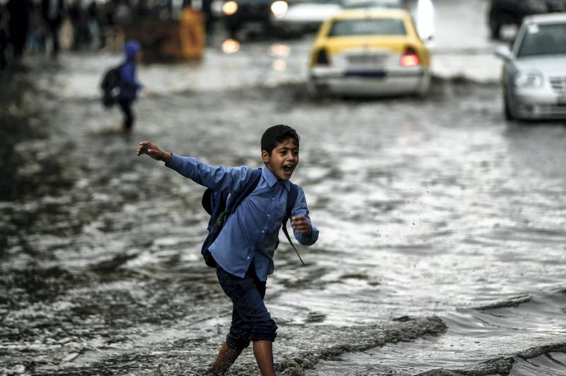 A young pupil crosses a flooded street during heavy rain in Gaza City on November 10, 2018. (Photo by MAHMUD HAMS / AFP)