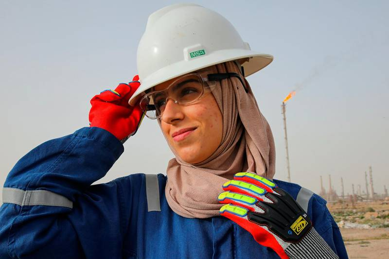 Zainab Amjad, a petrochemical engineer, poses for a photo near an oil field outside Basra, Iraq, Monday, Feb. 18, 2021. Amjad is among just a handful of women who have eschewed the dreary office jobs typically handed to female petrochemical engineers in Iraq. Instead, they chose to become trailblazers in the country's oil industry, taking up the grueling work of drilling. (AP Photo/Nabil al-Jourani)