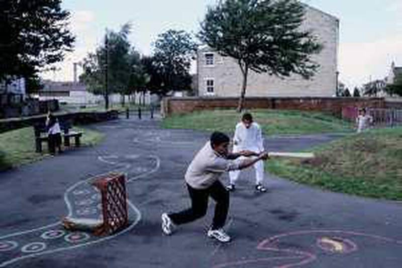 ca. 2001, Manningham, Bradford, West Yorkshire, England, UK --- Asian children play cricket in a park in Manningham, an area where primarily Asian Muslims live. --- Image by © Gideon Mendel/CORBIS