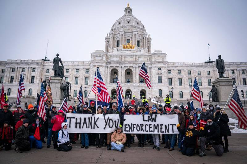 People pose with signs thanking law enforcement as Minnesota State troopers stand guard outside the Capitol during a rally supporting President Trump at the Minnesota Capitol, Saturday, Jan. 9, 2021 in St. Paul, Minn. State Patrol officers stood in a line and guarded the steps of the Minnesota Capitol on Saturday, as roughly 100 supporters of President Donald Trump gathered to protest the results of the 2020 election. (Leila Navidi/Star Tribune via AP)