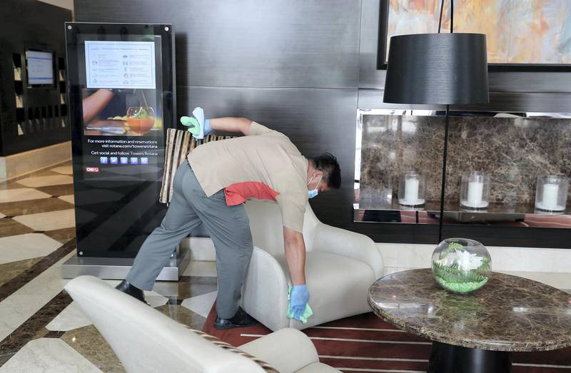 DUBAI, UNITED ARAB EMIRATES , July 8 – 2020 :- Cleaning staff disinfecting the sitting area at the Towers Rotana hotel on Sheikh Zayed road in Dubai. After each use, cleaning staff disinfect the sitting area at the reception as a  preventive measure against the spread of coronavirus. (Pawan Singh / The National) For News/Standalone/Online/Stock