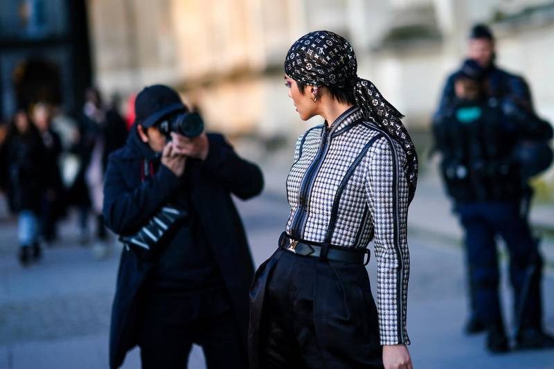 PARIS, FRANCE - MARCH 03: A guest wears a Vuitton monogram bandanna, a checked pattern black and white jacket, a belt, earrings, and poses in front of a photographer, outside Vuitton, during Paris Fashion Week - Womenswear Fall/Winter 2020/2021 on March 03, 2020 in Paris, France. (Photo by Edward Berthelot/Getty Images)
