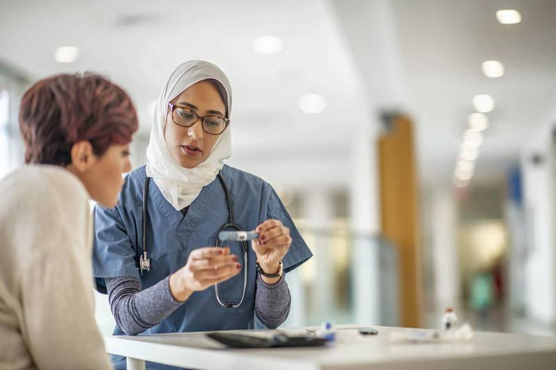 A female doctor of Middle Eastern ethnicity meets with a female patient. The doctor is wearing a hijab. The two women are seated at a table. The patient is diabetic and the doctor is holding an insulin pen and is explaining how to use the device. The patient is listening intently.