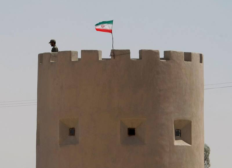 An Iranian anti-narcotics policeman stands guard in front of an Iranian flag on an observation tower in Milak on the road along Iran's southeastern border with Afghanistan on May 20, 2009. Iran gave foreign envoys to Tehran and journalists a rare tour on May 20 of its restive eastern border in a bid to raise awareness and much-needed funds for its war on drugs. The Islamic republic says it has spent about 800 million dollars over three years to deter drug running on its porous eastern frontier with Afghanistan and Pakistan. According to UN estimates, about 40 percent of the 7,700 tonnes of narcotics produced in Afghanistan last year entered Iran, which also faces serious drug abuse among its mostly youthful 70-million population.  AFP PHOTO/BEHROUZ MEHRI (Photo by BEHROUZ MEHRI / AFP)