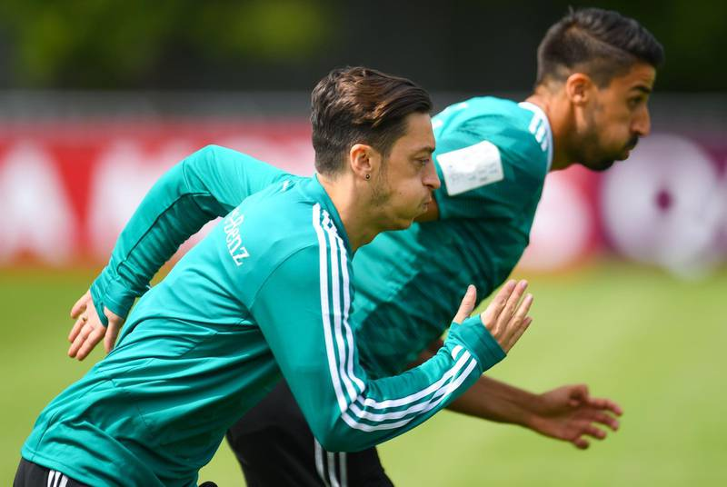 Germany's midfielders Mesut Ozil (L) and Sami Khedira warm up during a training session in Vatutinki, near Moscow, on June 14, 2018, ahead of the Russia 2018 World Cup football tournament.    -   / AFP / Patrik STOLLARZ