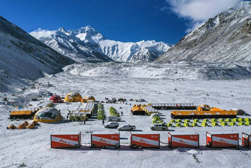 FILE - In this April 30, 2020, aerial file photo released by China's Xinhua News Agency, vehicles and tents are seen at the base camp at the foot of the Chinese side of the peak of Mount Qomolangma, also known as Mount Everest, in southwestern China's Tibet Autonomous Region. China has canceled attempts to climb Mount Everest from its side of the world's highest peak because of fears of importing COVID-19 cases from neighboring Nepal, state media reported. (Purbu Zhaxi/Xinhua via AP, File)