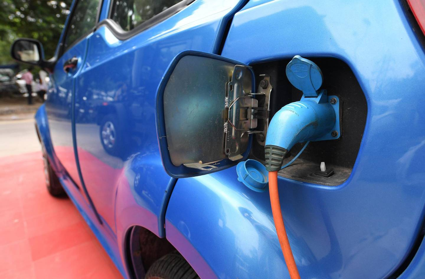 """This photo taken on July 21, 2017 shows Mahindra's electric car """"e2o Plus"""" plugged in for charging at a showroom in New Delhi. India will roll out nearly 100,000 battery-powered buses and autorickshaws onto its sulpherous, clogged city streets in coming weeks to set it on the road to make new vehicle sales all-electric by 2030. India, one of the world's most polluted nations, has one of the most ambitious plans to kick its fossil fuel addiction. Analysts say the target is """"daunting"""".  / AFP PHOTO / Prakash SINGH / TO GO WITH: India-automobile-pollution-technology, FOCUS by Megha BAHREE"""