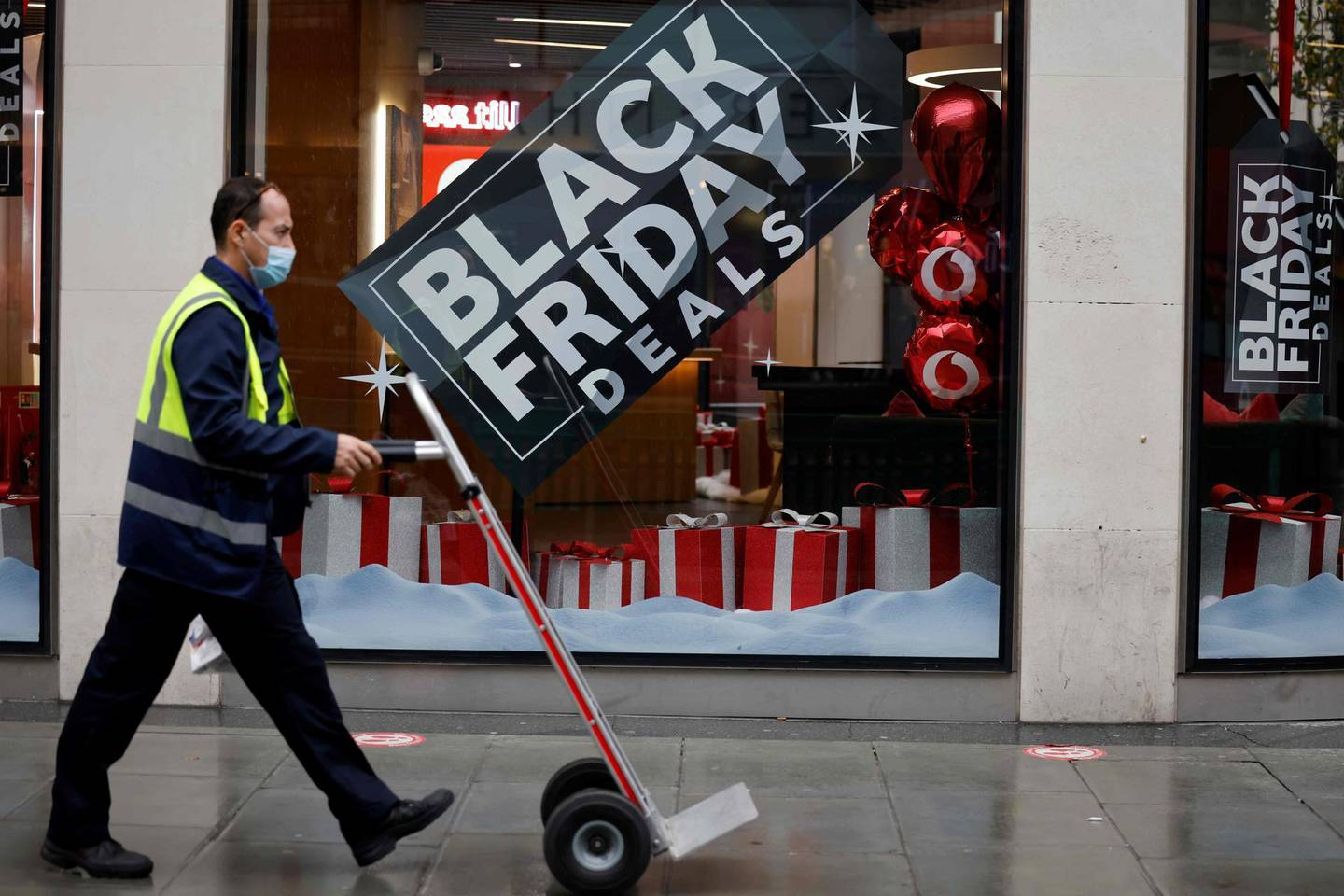 A delivery man walks in the rain past Black Friday offers in a shop in central London on November 20, 2020, as life under a second lockdown continues in England.  The current lockdown in England has shuttered restaurants, gyms and non-essential shops and services until December 2, with hopes business could resume in time for Christmas. / AFP / Tolga Akmen