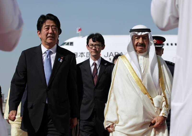 Japanese Prime Minister Shinzo Abe (L) is welcomed by Bahraini Prime Minister Khalifa bin Salman al-Khalifa (R) upon his arrival at the Bahraini airport in Muharraq, on August 24, 2013. AFP PHOTO/POOL/HASAN JAMALI (Photo by HASAN JAMALI / POOL / AFP)