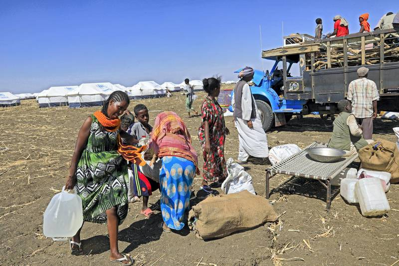 Ethiopian refugees, who fled the Tigray conflict, gather their belongings upon their arrival at the Tenedba camp in Mafaza, eastern Sudan on January 8, 2021, after being transported from the reception center. (Photo by ASHRAF SHAZLY / AFP)