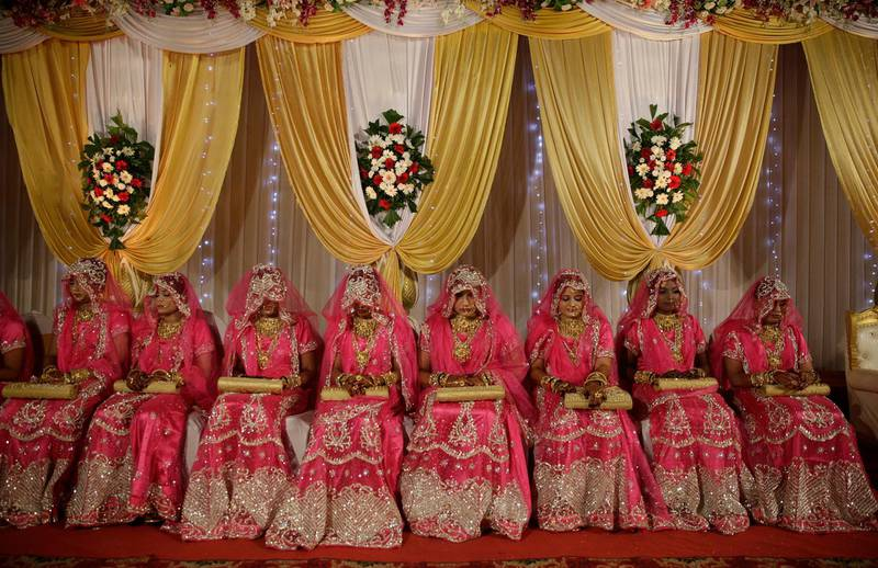 Brides sit for a mass marriage event in Mumbai, India, Monday, Nov. 20, 2017. Mass weddings in India are organized by social organizations primarily to help the economically backward families who cannot afford the high ceremony costs as well as the customary dowry and expensive gifts that are still prevalent in many communities. (AP Photo/RafiqMaqbool)