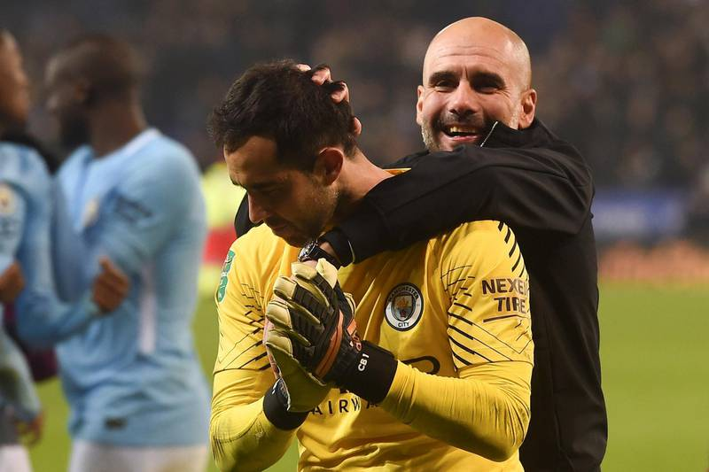 Manchester City's Spanish manager Pep Guardiola (R) celebrates on the pitch with Manchester City's Chilean goalkeeper Claudio Bravo (L) after winning after the penalty shoot out in the English League Cup quarter-final football match between Leicester City and Manchester City at King Power Stadium in Leicester, central England on December 19, 2017. (Photo by PAUL ELLIS / AFP) / RESTRICTED TO EDITORIAL USE. No use with unauthorized audio, video, data, fixture lists, club/league logos or 'live' services. Online in-match use limited to 75 images, no video emulation. No use in betting, games or single club/league/player publications. /