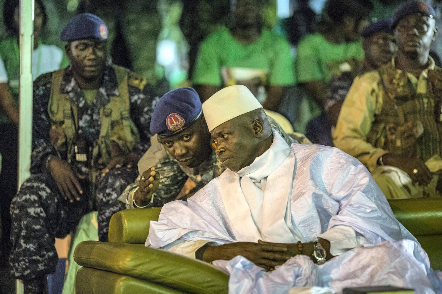 """Incumbent Gambian President Yahya Jammeh listens to one of his aides in Banjul on November 29, 2016, during the closing rally of the electoral campaign of the Alliance for Patriotic Reorientation and Construction (APRC). - More than 880,000 voters are expected to cast their ballots when the west African country goes to the polls on December 1, 2016. Jammeh has won four elections with his ruling Alliance for Patriotic Reorientation and Construction, following a 2002 constitutional amendment lifting term limits. Rights bodies and media watchdogs including Reporters Without Borders (RSF) accuse Jammeh of cultivating a """"pervasive climate of fear"""" and of crushing dissent against his regime, one cause of the mass exodus of Gambian youths to Europe. (Photo by MARCO LONGARI / AFP)"""