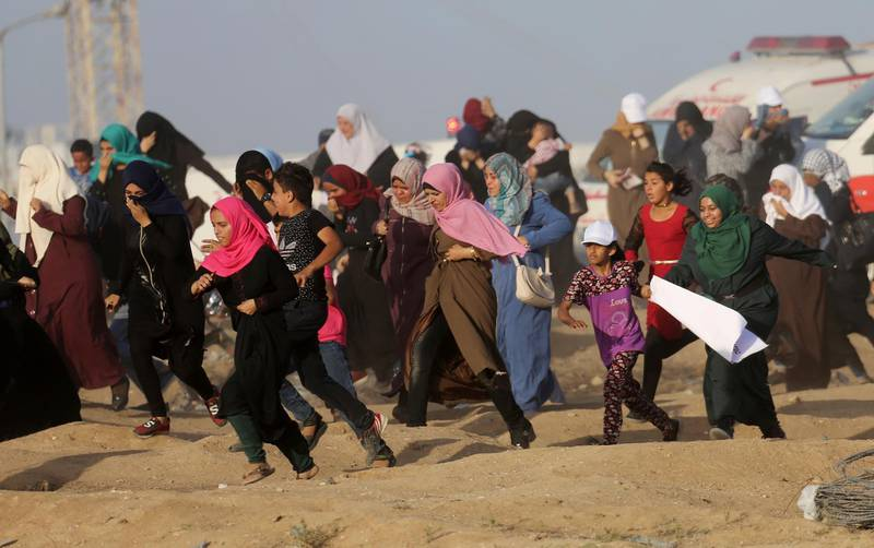 Palestinian women protesters run for cover from teargas fired by Israeli troops during a protest near the Gaza Strip's border with Israel, east of Gaza City, Tuesday, July 3, 2018. (AP Photo/Adel Hana)