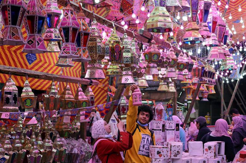 """People take a photo of a traditional Ramadan lantern called """"fanous"""" at a shop stall ahead of the Muslim holy month of Ramadan, amid the coronavirus disease (COVID-19) pandemic in Cairo, Egypt, April 8, 2021. REUTERS/Mohamed Abd El Ghany"""