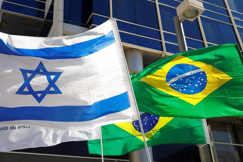 """TOPSHOT - In this photo taken on October 28, 2018, the Israeli and Brazilian flags hang outside the building housing the offices of the Brazilian Embassy, in the Israeli city of Tel Aviv. Israeli Prime Minister Benjamin Netanyahu on November 1, hailed as """"historic"""" Brazilian president-elect Jair Bolsonaro's plan to move his country's embassy from Tel Aviv to Jerusalem. / AFP / JACK GUEZ"""