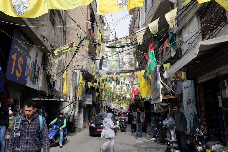 """A picture taken on December 21, 2017 shows a view of posters showing Palestinian leaders and Fatah flags hanging in a street in the Burj al-Barajneh camp, a southern suburb of the Lebanese capital Beirut.More than 174,000 Palestinian refugees live in Lebanon, authorities announced on December 21, in the first-ever census of its kind for a country where demographics have long been a sensitive subject.The census was carried out by the government's Lebanese-Palestinian Dialogue Committee in 12 Palestinian camps as well as 156 informal """"gatherings"""" across the country. / AFP PHOTO / ANWAR AMRO"""