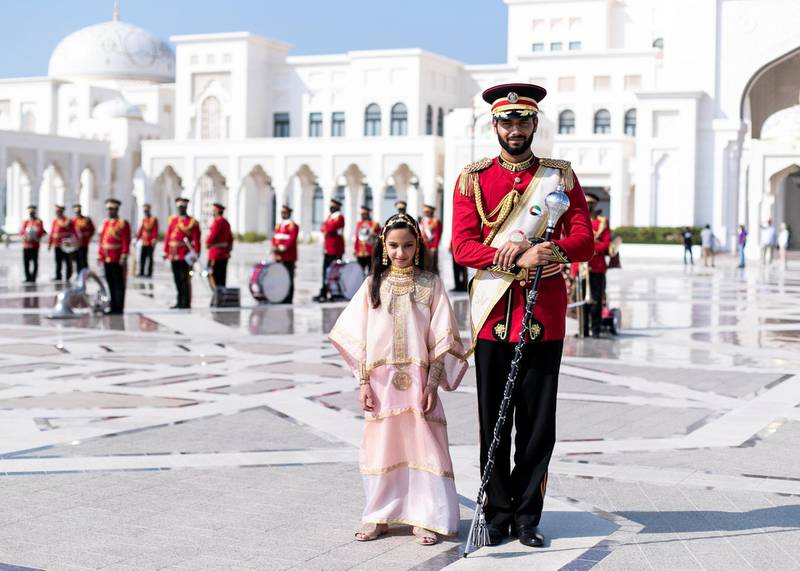ABU DHABI, UNITED ARAB EMIRATES. 2 DECEMBER 2019. Afra Al Mansoori poses next to a Abu Dhabi's Police band member during UAE's National Day celebrations at Qasr Al Watan.(Photo: Reem Mohammed/The National)Reporter:Section:
