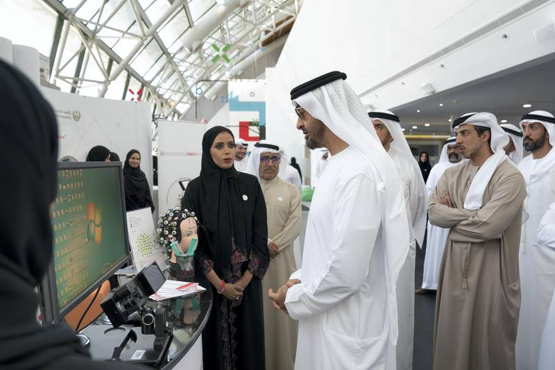 AL AIN, ABU DHABI, UNITED ARAB EMIRATES - February 7, 2019: HH Sheikh Mohamed bin Zayed Al Nahyan, Crown Prince of Abu Dhabi and Deputy Supreme Commander of the UAE Armed Forces (C), speaks with students while visiting UAE University in Al Ain. Seen with HH Sheikh Mansour bin Zayed Al Nahyan, UAE Deputy Prime Minister and Minister of Presidential Affairs (back 2nd R), and HE Mohamed Mubarak Al Mazrouei, Undersecretary of the Crown Prince Court of Abu Dhabi (back R).  ( Ryan Carter / Ministry of Presidential Affairs ) ---