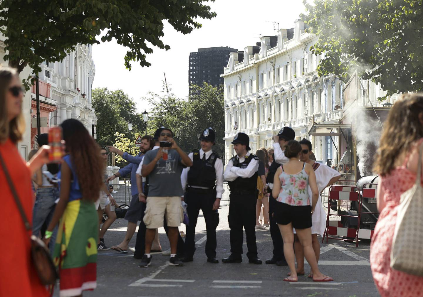 Police secure the area, blocking the road towards the burned out Grenfell Tower apartment block, during the Family Day at the Notting Hill Carnival in west London, Sunday Aug. 27, 2017. The police presence in London has been stepped up because of the holiday weekend and the annual Notting Hill Carnival, a busy weekend street festival that attracts huge crowds. (Yui Mok/PA via AP)