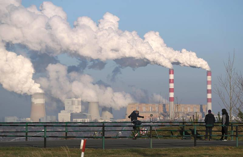 ROGOWIEC, POLAND - NOVEMBER 29: Steam and smoke rise from the Belchatow Power Station as young men film a rap music video at a viewing point over the open-pit coal mine that feeds Belchatow with coal on November 29, 2018 in Zlobnica near Rogowiec, Poland. The Belchatow station, with an output of 5,472 megawatts, is the world's largest lignite coal-fired power station. The station emits approximately 30 million tonnes of CO2 per year. The United Nations COP 24 climate conference is due to begin on December 2 in nearby Katowice, two hours south of Belchatow.  (Photo by Sean Gallup/Getty Images)