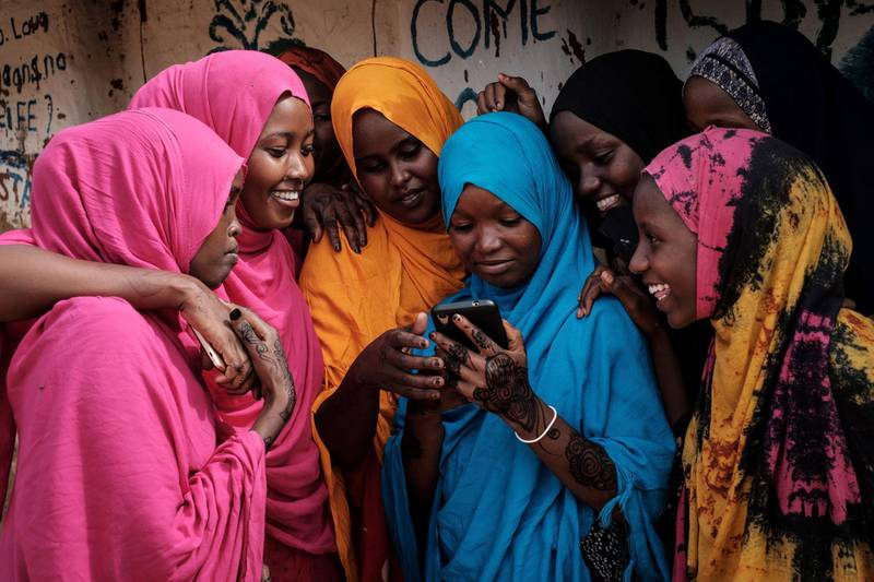 Young Somali refugee women look at a smartphone as they stand together at Dadaab refugee complex, in the north-east of Kenya, on April 16, 2018. - The Dadaab refugee complex which has some 235269 refugees and asylum seekers in four camps about 80kms from the Somali-Kenyan border was established in 1991, according to UNHCR camp population statistics in January 2018. (Photo by Yasuyoshi CHIBA / AFP)