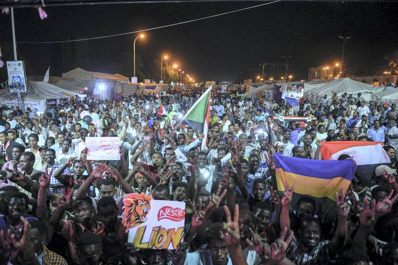Sudanese protesters wave flags and flash victory signs as they gather for a sit-in outside the military headquarters in Khartoum on May 19, 2019. - Talks between Sudan's ruling military council and protesters are set to resume, army rulers announced, as Islamic movements rallied for the inclusion of sharia in the country's roadmap. (Photo by Mohamed el-Shahed / AFP)
