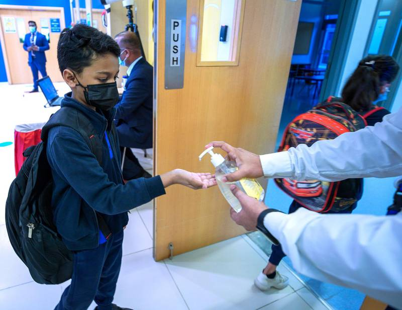 Abu Dhabi, United Arab Emirates, February 14, 2021. Pupils return to Abu Dhabi's private schools. GEMS United Indian School – Abu Dhabi.  Students hands are sanitized after getting temperature checked at the lobby before entering the classroom area.Victor Besa/The NationalSection: NAReporter:  Anam Rizvi