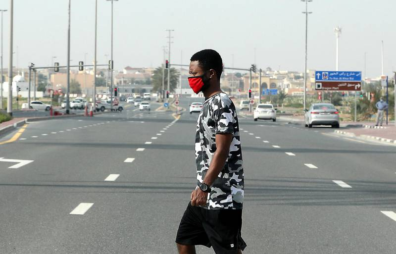 DUBAI, UNITED ARAB EMIRATES , April 18– 2020 :- A pedestrian wearing a face mask crosses the street in International City in Dubai. Only two entrance are open for vehicles coming from Al Awir road before the Dragon Mart 1 and Manama Street to International City in Dubai.  Dubai is conducting 24 hours sterilisation programme across all areas and communities in the Emirate and told residents to stay at home. UAE government told residents to wear face mask and gloves all the times outside the home whether they are showing symptoms of Covid-19 or not.  (Pawan Singh / The National) For News/Online