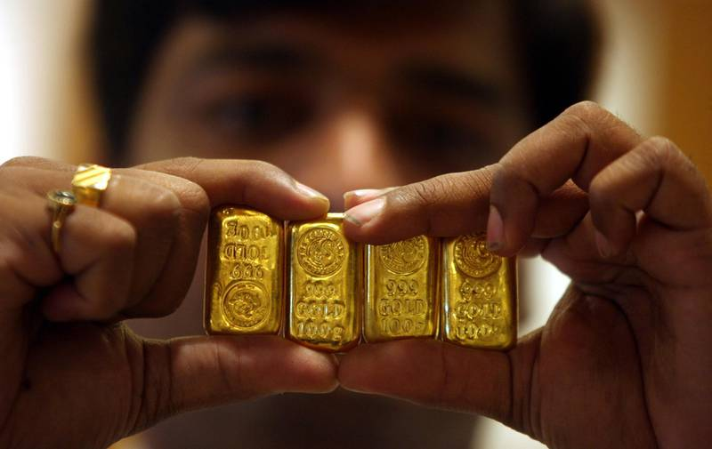 FILE PHOTO: A salesman displays gold bars inside a jewellery shop on the occasion of the Akshaya Tritiya festival in the southern Indian city of Hyderabad May 6, 2011. Gold jewellery is a popular gift at marriages and festivals in India. REUTERS/Krishnendu Halder/File Photo