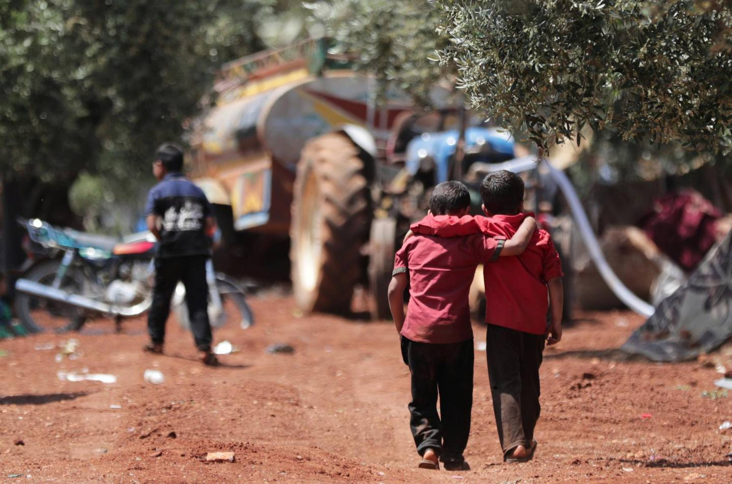 Displaced Syrian children walk together in an olive grove at Atmeh town, Idlib province, Syria May 15, 2019. Picture taken May 15, 2019. REUTERS/Khalil Ashawi