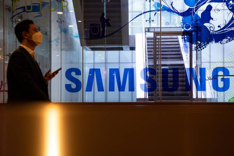 A man wearing a protective mask walks past the Samsung Electronics Co. signage at the company's D'light flagship store in Seoul, South Korea, on Tuesday, Oct. 6, 2020. Samsungwere among a list of global firms that were cleared by India's Ministry of Electronics and Information Technologythat won approval to manufacture products in India under a plan aimed at attracting investment of more than 10.5 trillion rupees ($143 billion) for mobile-phone production over the next five years. Photographer: SeongJoon Cho/Bloomberg