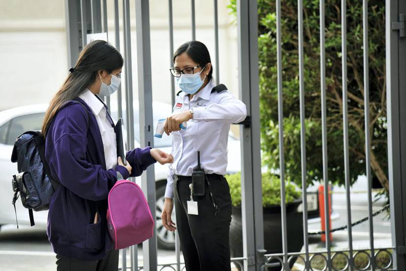 A student in protective face mask gets her temperature checked at the entrance of Al-Mizhar American Academy as the government re-opens schools after months in the wake of Covid-19 pandemic in Dubai, UAE, Sunday, Aug. 30, 2020. (Photos by Shruti Jain - The National)