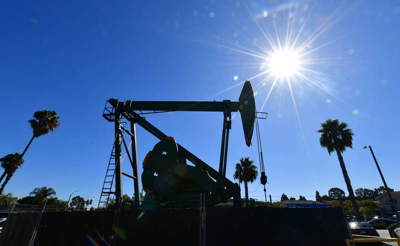 (FILES) In this file photo taken on October 21, 2019 A pumpjack from California-based energy company Signal Hill Petroleum is seen in front of the landmark Curley's Cafe, one of two pumpjacks in the Diner's parking lot which has been churning out oil from the ground below since 1921 in Signal Hill, California on October 21, 2019.  Despite the coronavirus pandemic that is devastating the world economy and oil demand, crude oil production continues at full steam, particularly in Saudi Arabia and the United States, pushing storage capacity to its limits.  / AFP / Frederic J. BROWN / TO GO WITH AFP STORY BY KEVIN TRUBLET