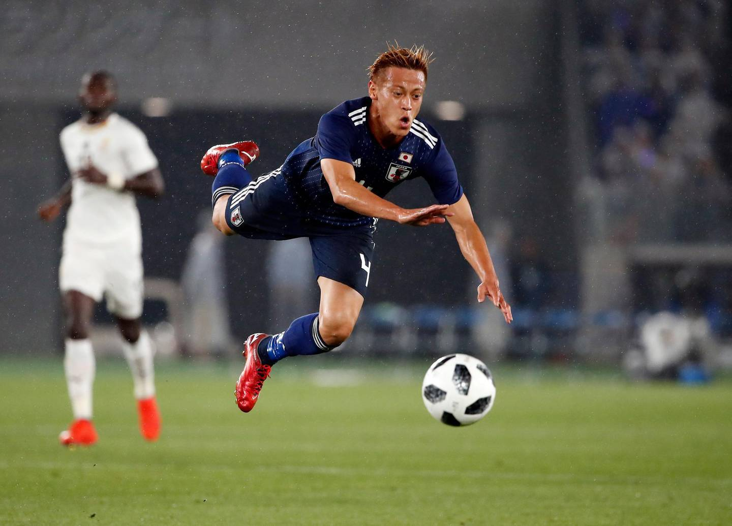 epa06773229 Japan's midfielder Keisuke Honda falls after colliding with Ghana's defender Andrew Kyere-Yiadom (not pictured) during a friendly soccer match between Japan and Ghana in Yokohama, near Tokyo, Japan, 30 May 2018.  EPA/FRANCK ROBICHON