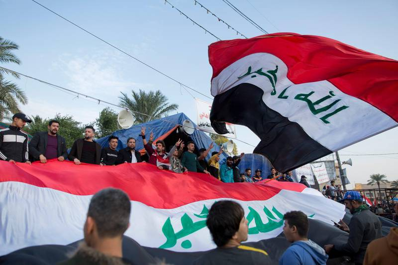 Activists chant anti-government slogans and fly big Iraqi flags at Tahrir square, in Baghdad, Iraq, Tuesday, Dec. 10, 2019. Thousands of Iraqi protesters celebrated the two-year anniversary of the defeat of the Islamic State group amid protests and public anger. (AP Photo/Nasser Nasser)