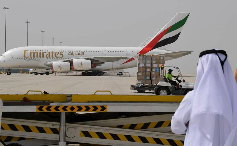 (FILES) In this file photo taken on March 2, 2020 medical equipment and coronavirus testing kits provided bt the World Health Organisation are pictured passing by an Emirates airlines Airbus A380-861, at the al-Maktum International airport in Dubai, as it is prepared to be delivered to Iran with a United Arab Emirates military transport plane.   Emirates airline has cut a tenth of its workforce during the novel coronavirus pandemic in layoffs that could rise to 15 percent, or 9,000 jobs, its president said, according to a report today.  / AFP / KARIM SAHIB