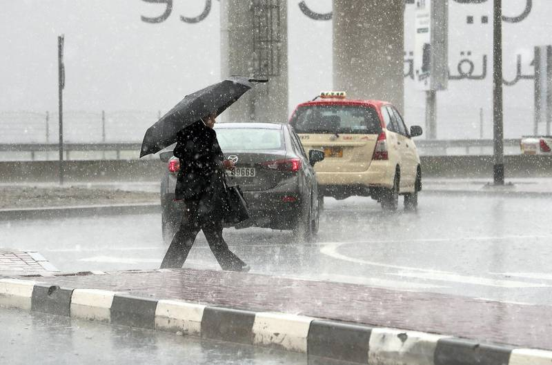 DUBAI, UNITED ARAB EMIRATES , March 22 – 2020 :- One of the commuter caught in the heavy rain in Al Barsha in Dubai. (Pawan Singh / The National) For News/Online/Instagram.