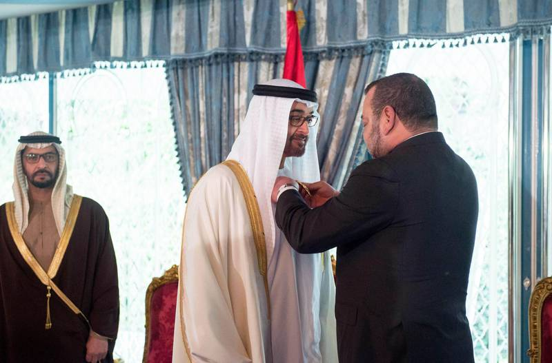 CASABLANCA, MOROCCO - March 17, 2015: HM King Mohammed VI of Morocco (R), presents HH Sheikh Mohamed bin Zayed Al Nahyan Crown Prince of Abu Dhabi and Deputy Supreme Commander of the UAE Armed Forces (C), with The Order of Muhammadi Medal of the First Degree ( Wissam Al Muhammadi ), at the Royal Palace of Casablanca. Witnessing the honor is HH Sheikh Hamdan bin Zayed Al Nahyan UAE Deputy Prime Minister and Ruler of the Western Region (L).( Rashed Al Mansoori / Crown Prince Court - Abu Dhabi )