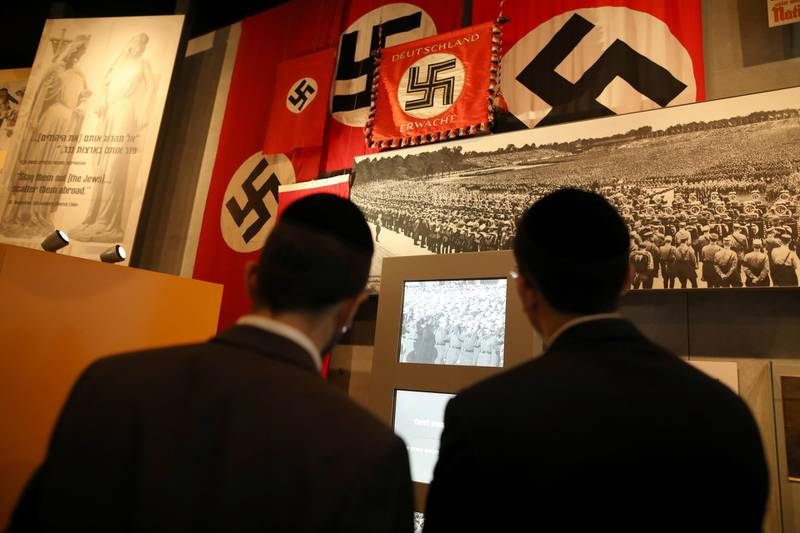 FILE PHOTO: Nazi German flags bearing swastikas are seen as visitors look at part of an exhibition in the Holocaust History Museum at the Yad Vashem World Holocaust Remembrance Center in Jerusalem January 15, 2020. REUTERS/Ammar Awad/File Photo