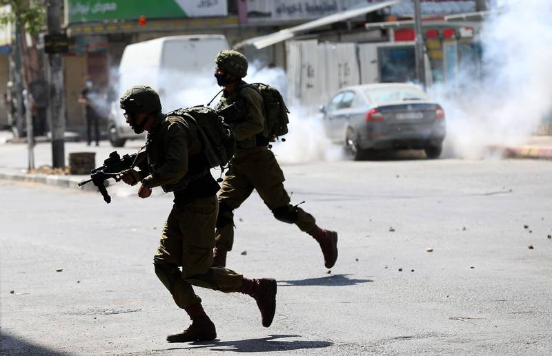 epa08530952 Israeli soldiers take up position during clashes with Palestinian protesters in the West Bank City of Hebron, 06 July 2020. Palestinians are protesting against an expected Israeli move to annex parts of the West Bank and Jordan Valley occupied by Israel since the 1967 Middle East war. The annexation move is supported by the Israeli-Palestinian Peace Plan of US President Donald Trump, unveiled in January 2020, but widely rejected in the region.  EPA/ABED AL HASHLAMOUN