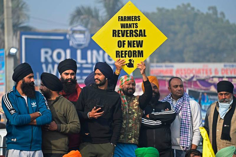 A farmer holds a placard during a nationwide general strike to protest against the recent agricultural reforms at the Delhi-Haryana state border in Singhu on December 8, 2020.  / AFP / Sajjad HUSSAIN