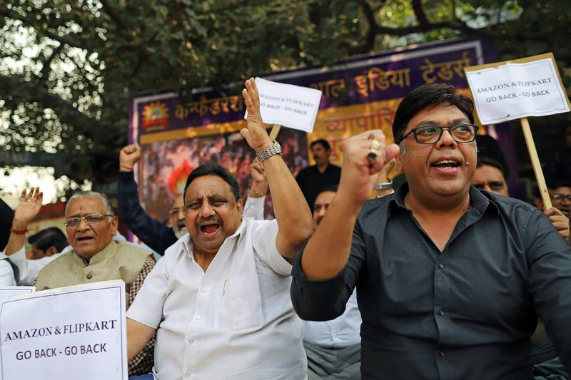 Merchants display placards and shout slogans during a sit-in protest at Sadar Bazaar in New Delhi, India, on Wednesday, Nov. 20, 2019. In the heart of New Delhi's largest wholesale bazaar, merchants who normally compete with each other have united against a common enemy. The sit-in, which created more chaos than usual among the rickshaws, motorbikes and ox-carts plying the market road, was one of as many as 700 protests againstAmazon.com Inc.andWalmart Inc.-- owner of local e-commerce leader Flipkart -- that organizers say took place at bazaars across India on a recent Wednesday. Photographer: Anindito Mukherjee/Bloomberg