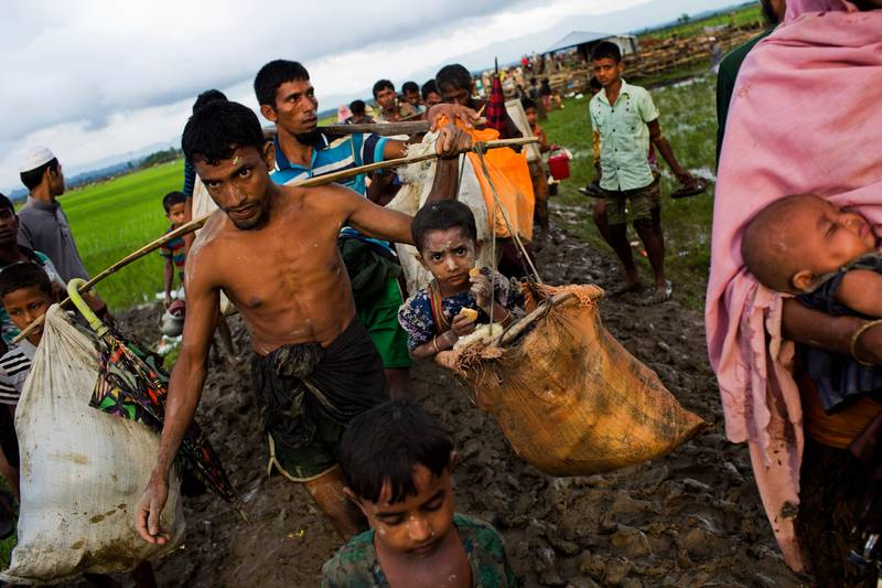 A Rohingya ethnic minority refugee from Myanmar carries a child in a sack and walks through rice fields after crossing over to the Bangladesh side of the border near Cox's Bazar's Teknaf area, Friday, Sept. 1, 2017. Myanmar's military says almost 400 people have died in recent violence in the western state of Rakhine triggered by attacks on security forces by insurgents from the Rohingya. Advocates for the Rohingya, an oppressed Muslim minority in overwhelmingly Buddhist Myanmar, say hundreds of Rohingya civilians have been killed by security forces. Thousands have fled into neighboring Bangladesh. (AP Photo/Bernat Armangue)