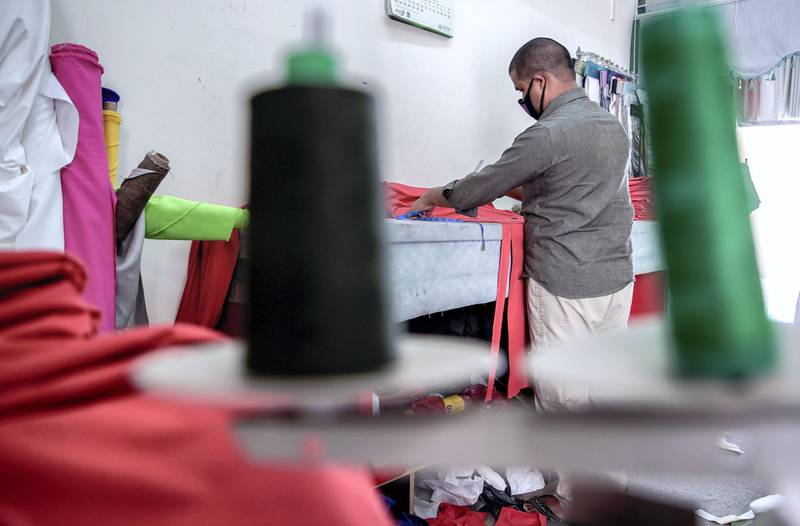 Abu Dhabi, United Arab Emirates, April 18, 2020.  The Carpet Souk at the Zayed Port area.  An   upholsterer cuts fabric for a Ramadan sofa.Victor Besa / The NationalSection:  NAFor:  Standalone/Stock Images
